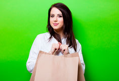 Portrait of young woman with shopping bags. Portrait of the beautiful young woman with shopping bags on the green background Stock Photos