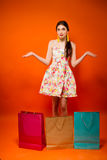 Portrait of young woman with shopping bags. Orange background Royalty Free Stock Photos