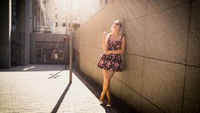 Portrait of beautiful young woman in short dress leaning against stone wall on city street and looking in camera royalty free stock image