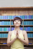 Portrait of young woman with short hair doing yoga with hands clasped together in front Stock Image