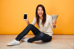 Portrait of a young woman showing blank screen mobile phone. Portrait of a happy young woman showing blank screen mobile phone and money banknotes while sitting Royalty Free Stock Photography