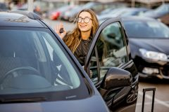 Woman renting a car. Portrait of a young woman showing keys near the rental car on the parking Stock Photo