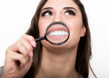 Portrait of young woman showing teeth and tongue through magnifying glass Royalty Free Stock Photos
