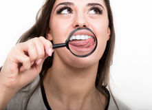 Portrait of young woman showing teeth and tongue through magnifying glass Royalty Free Stock Photography
