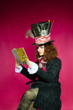 Portrait of young woman in the similitude of the Hatter (. Alice's Adventures in Wonderland) reading book royalty free stock images