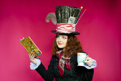 Portrait of young woman in the similitude of the Hatter (. Alice's Adventures in Wonderland), red background royalty free stock photo