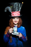 Portrait of young woman in the similitude of the Hatter with cup royalty free stock photography