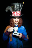 Portrait of young woman in the similitude of the Hatter (. Portrait of young woman in the similitude of the Hatter with cup of tea (Alice's Adventures in royalty free stock image