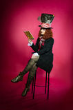 Portrait of young woman in the similitude of the Hatter reading Stock Image