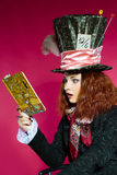 Portrait of young woman in the similitude of the Hatter reading. Portrait of young woman in the similitude of the Hatter (Alice's Adventures in Wonderland) royalty free stock photos