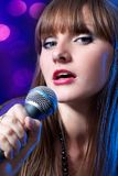Portrait young Woman Singing into Microphone Stock Photo