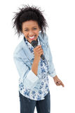 Portrait of a young woman singing into a microphone Royalty Free Stock Photography