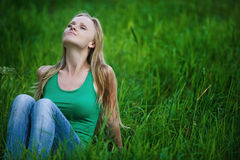 Portrait young woman sits on green grass Stock Image