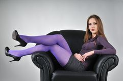 Portrait of young woman sitting. Portrait of young woman with violet pantyhose sitting in big armchair - studio shot Royalty Free Stock Image