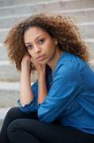 Portrait of a young woman sitting alone outdoors Royalty Free Stock Photo