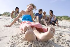 Portrait of young woman sitting at beach, friends in background Stock Photos