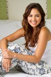 Young woman sitting on the bed laughing. Portrait of a young woman sitting on the bed laughing Royalty Free Stock Photography