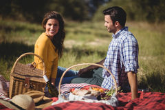 Portrait of young woman sitting with boyfriend on picnic blanket Stock Photo