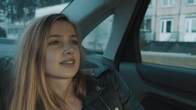 Portrait of young woman sitting on car backseat moving along city street stock footage