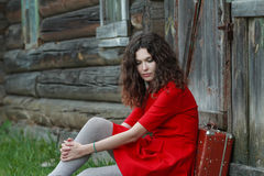 Portrait of young woman sitting in front of old Stock Photography