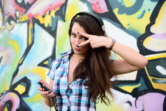 Portrait of young woman sitting at graffiti wall Royalty Free Stock Image