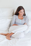 Portrait of a young woman sitting on her bed Stock Images