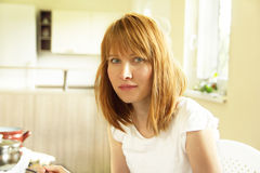 Portrait of young woman sitting in kitchen Royalty Free Stock Images