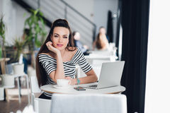 Portrait of young woman sitting with laptop and mobile phone in a sidewalk cafe. Stock Photo