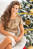 Portrait of young woman sitting near christmas tree stock photo