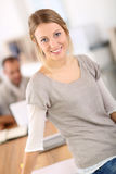 Portrait of young woman sitting on office desk Royalty Free Stock Photography