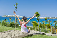 Portrait of young woman sitting with open arms in a tropic sea garden Royalty Free Stock Photo