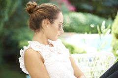 Young woman deep in thought. Portrait of young woman sitting outdoor and looking deep in thought stock images
