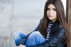 Portrait of a young woman sitting on the sidewalk. Royalty Free Stock Photography