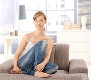 Portrait of young woman sitting on sofa Royalty Free Stock Photography