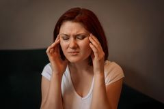 Portrait of a young woman sitting on a sofa with closed eyes and fingers pressed to her temples. Health issues, migraine, headache stock images
