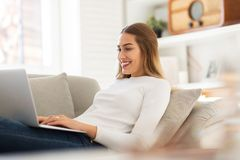 Woman sitting on sofa with her laptop royalty free stock photos