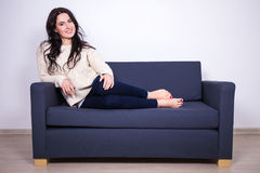 Portrait of young woman sitting on sofa at home Royalty Free Stock Images