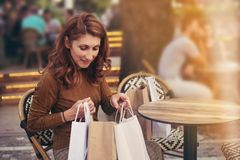 Portrait of young woman sitting in street cafe looking through her shopping bags stock image