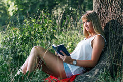 Portrait of young woman sitting under a tree. Outdoor portrait of young woman sitting in the park under a tree and reading a book Royalty Free Stock Images