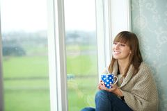 Young Woman Sitting by Window with Cup of Tea Stock Photos
