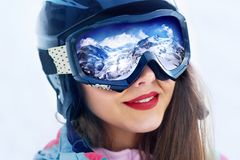 Portrait of young woman at the ski resort on the background of mountains and blue sky.A mountain range reflected in the ski mask. Portrait of young woman at the Royalty Free Stock Image