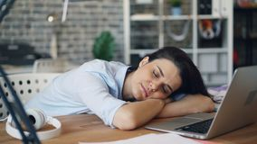 Portrait of young woman sleeping on desk relaxing at work indoors. Lying on table top with eyes closed near laptop. People, business and youth concept stock footage