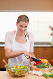 Portrait of a young woman slicing vegetables. In her kitchen Royalty Free Stock Photo