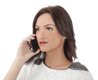 Portrait of a Young Woman on a Smartphone. Portrait of a young brown haired woman on a mobile phone isolated against a white background Royalty Free Stock Photography