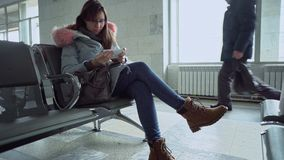 Portrait of young woman with smartphone sitting at train station. stock video
