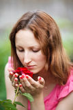 Portrait of young woman smelling rose in garden Stock Image