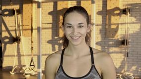 The portrait young woman smiling during the break in the fitness training in the gym. The caucasian athlete in sportswear stands in the room with equipment on stock video