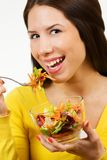 Portrait of a young woman, smiling and eating a bowl of salad royalty free stock photography