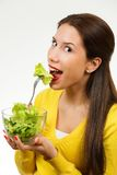 Portrait of a young woman, smiling and eating a bowl of salad stock photos