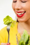 Portrait of a young woman, smiling and eating lettuce Stock Photos